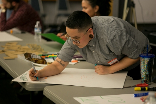 Adrian making a poster at an ACLU SoCal 2018 Women's March poster party.