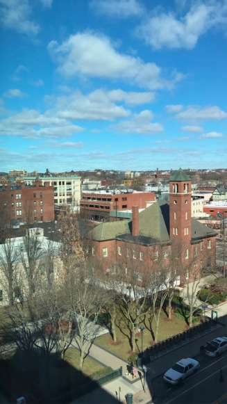 [Image Description: A photo of trees, brick buildings, and a cloudy sky in Cambridge, Massachusetts ]